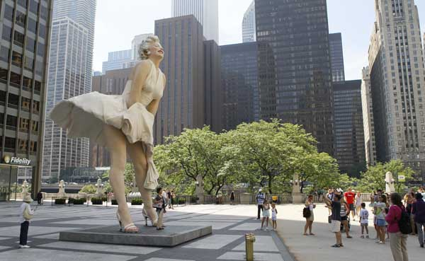 The curious gather around Seward Johnson&#39;s 26-foot-tall sculpture of Marilyn Monroe, in her most famous wind-blown pose, on Michigan Ave. Friday, July 15, 2011 in Chicago.  <span class=meta>(AP Photo&#47;Charles Rex Arbogast)</span>